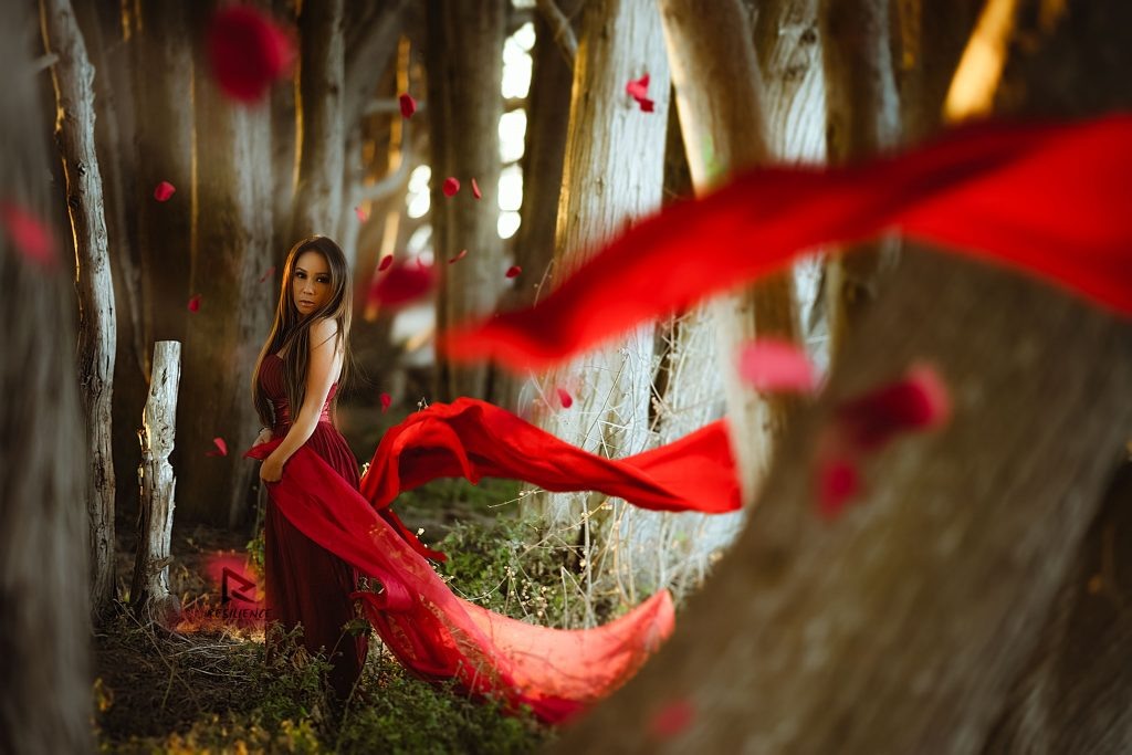 Asian girl in red with raining roses and red flowing dress