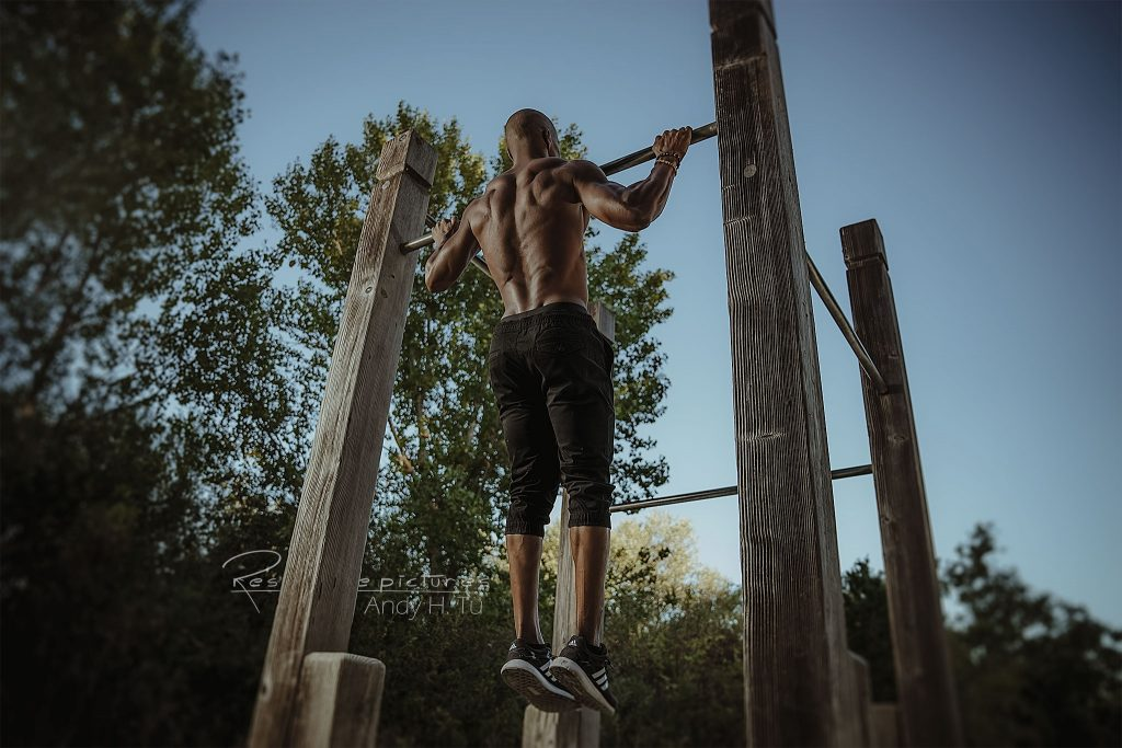 Athlete with strong muscular lats doing pull ups