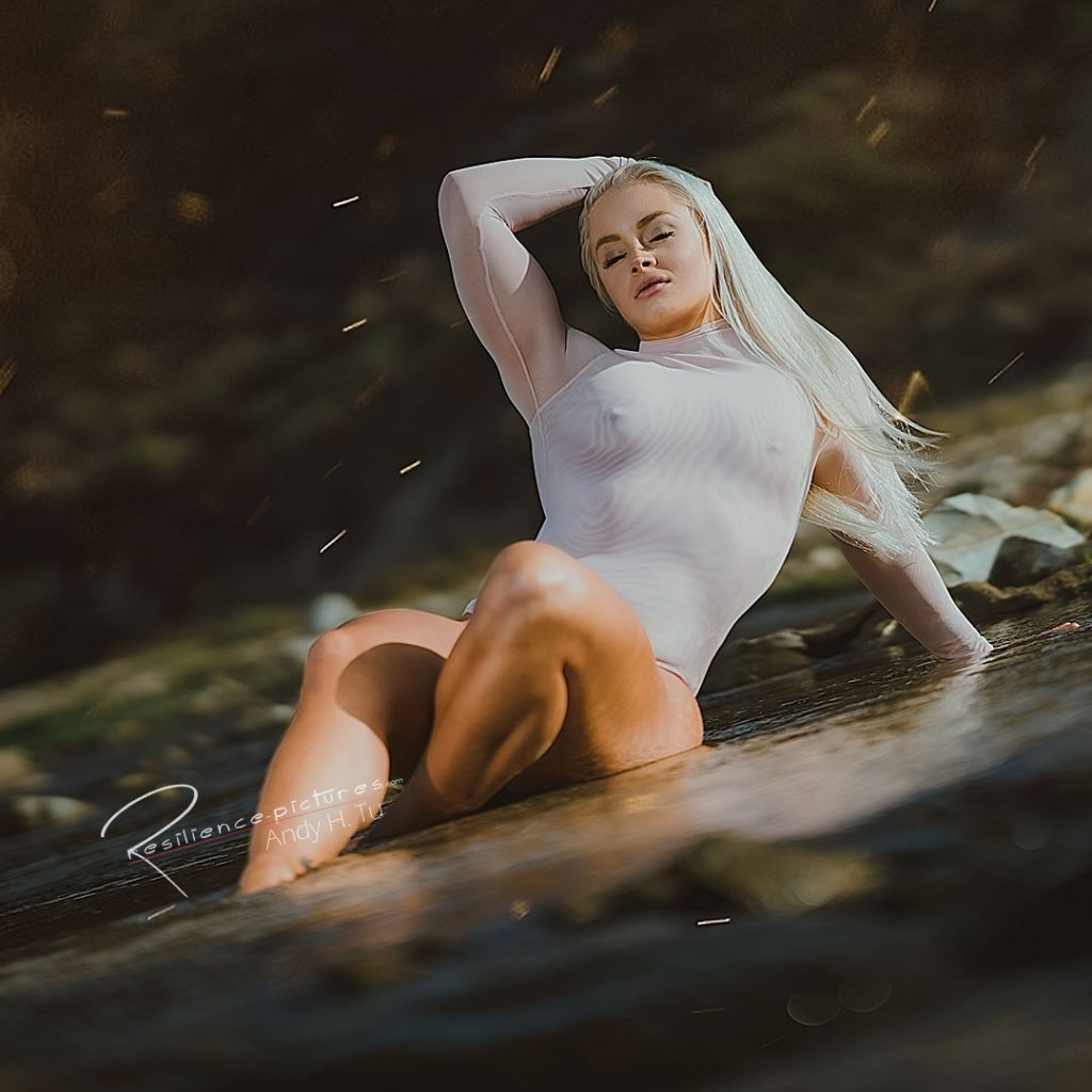 Blonde swedish girl sitting in a river with her pink one piece