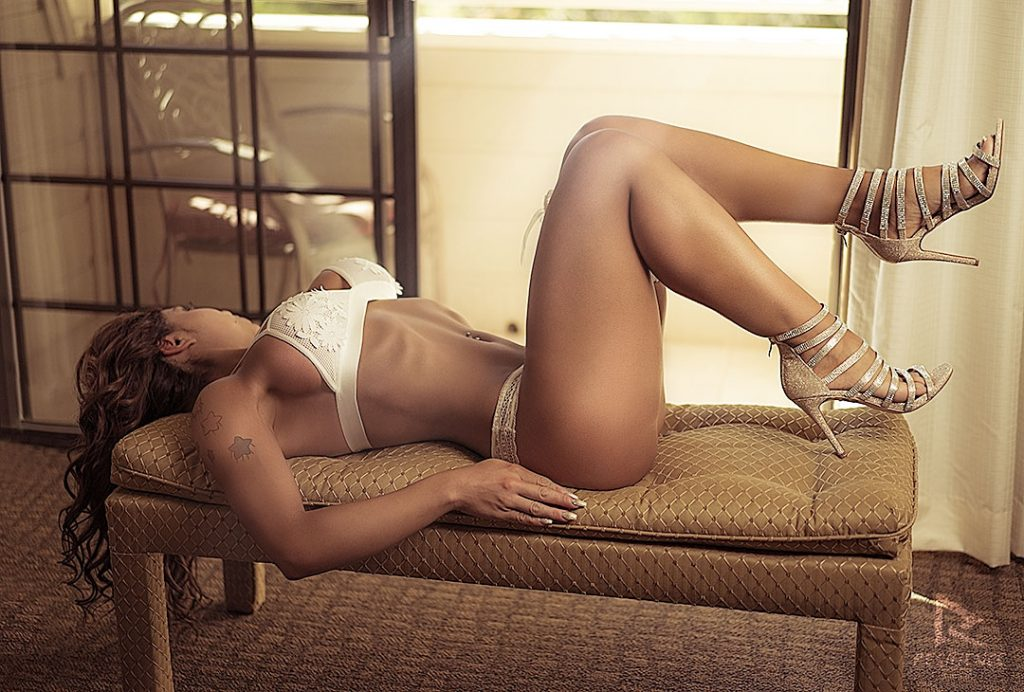 Boudoir-model-in-white-lingerie-looking-out-the-window-laying-on-a-bench