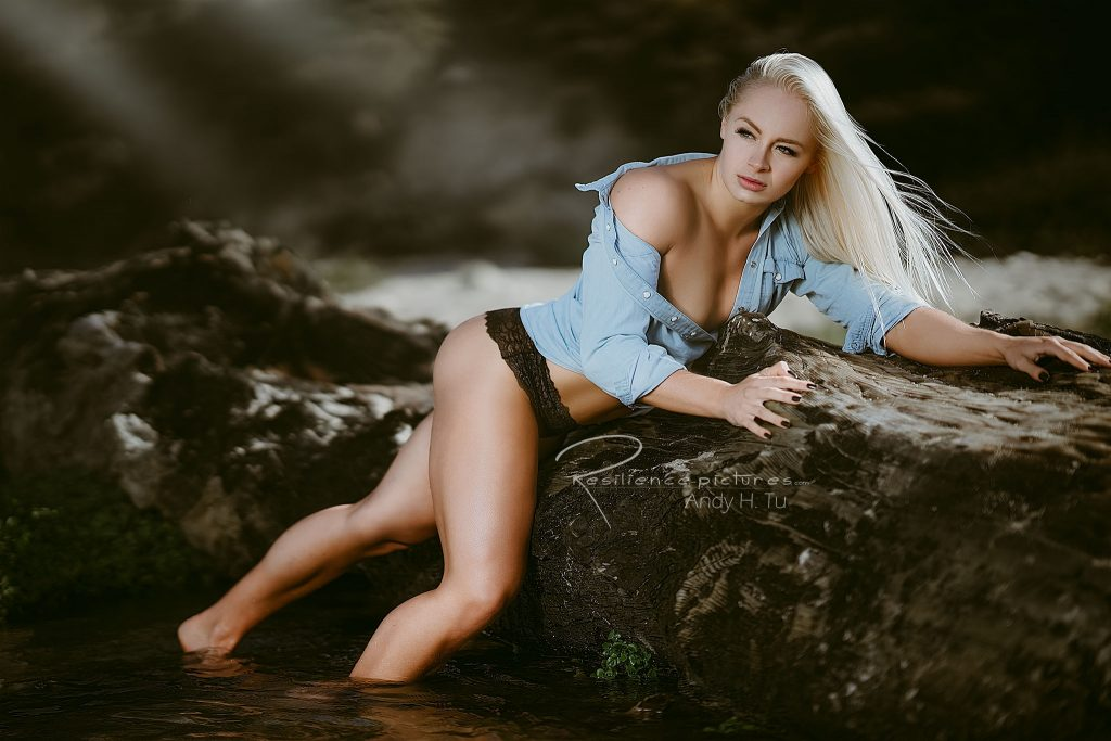 blonde girl in denim, posting for a photo shoot on a beach
