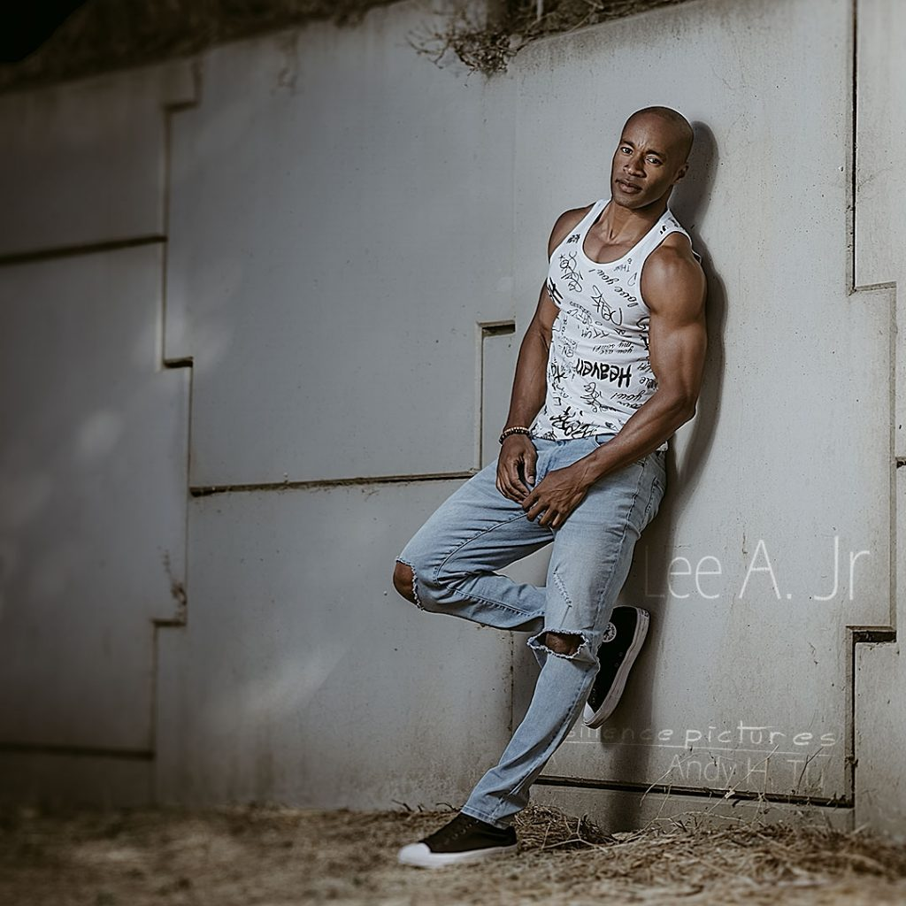 fit guy posing against a wall in denim and converse