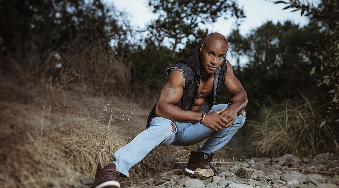 male model in denim crouched for a fitness shoot outdoor