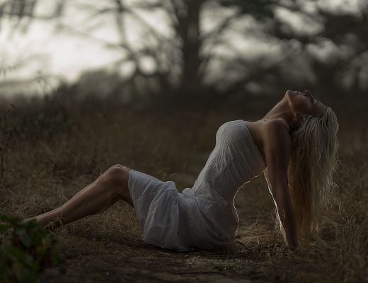 relieved-woman-sitting-on-the-grass-in-muted-light