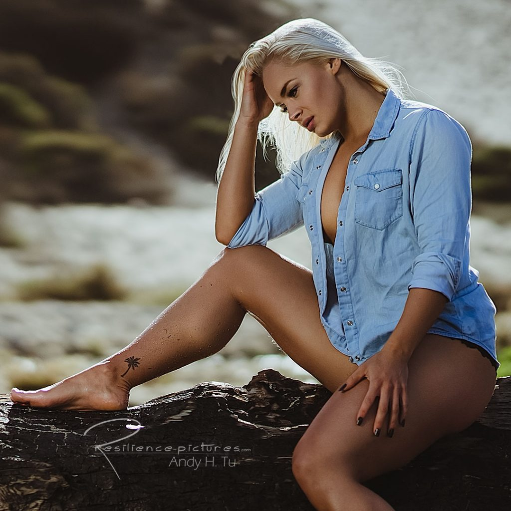swedish girl in denim, thinking on a wet log at the beach