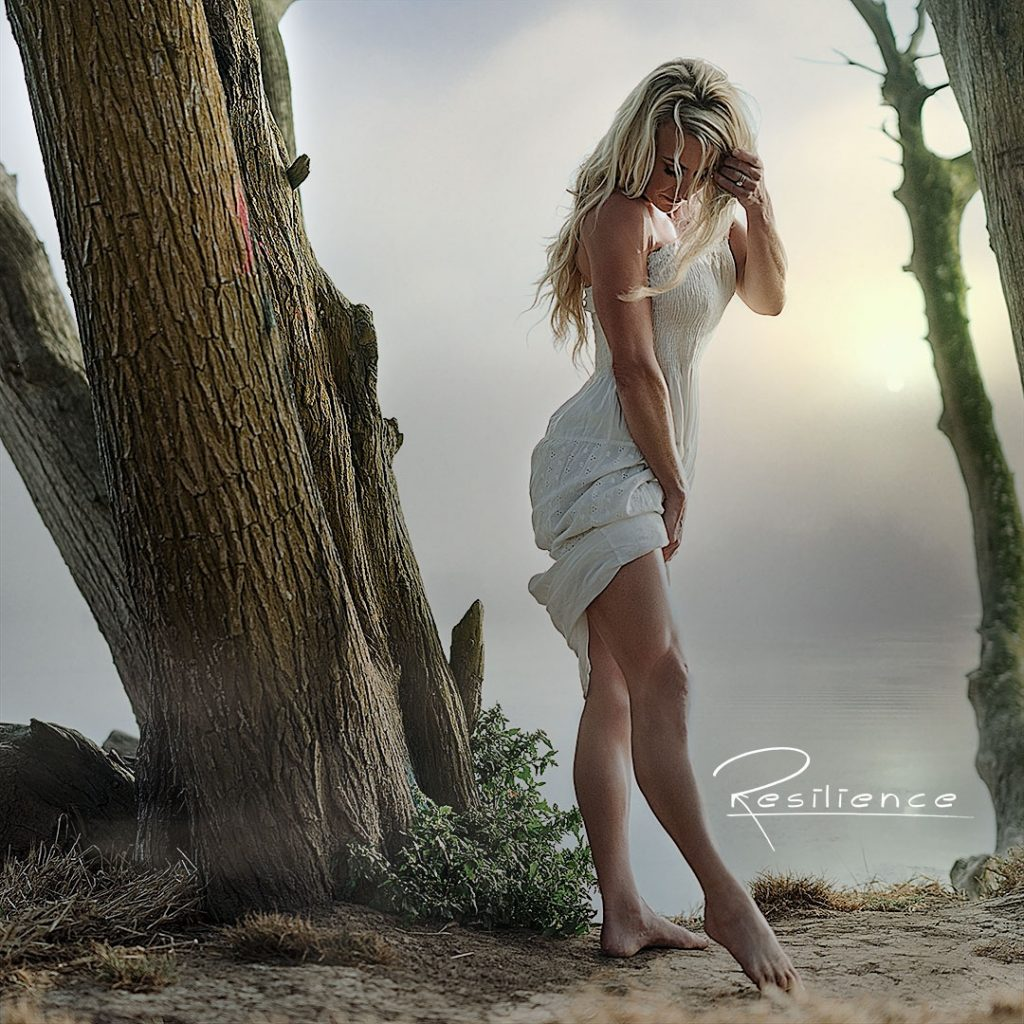 woman-in-white-dress-at-foggy-beac-looking-down