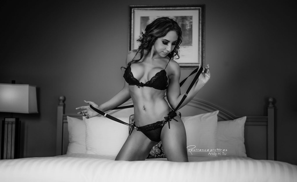 Boudoir model in black lingerie posing on her bed