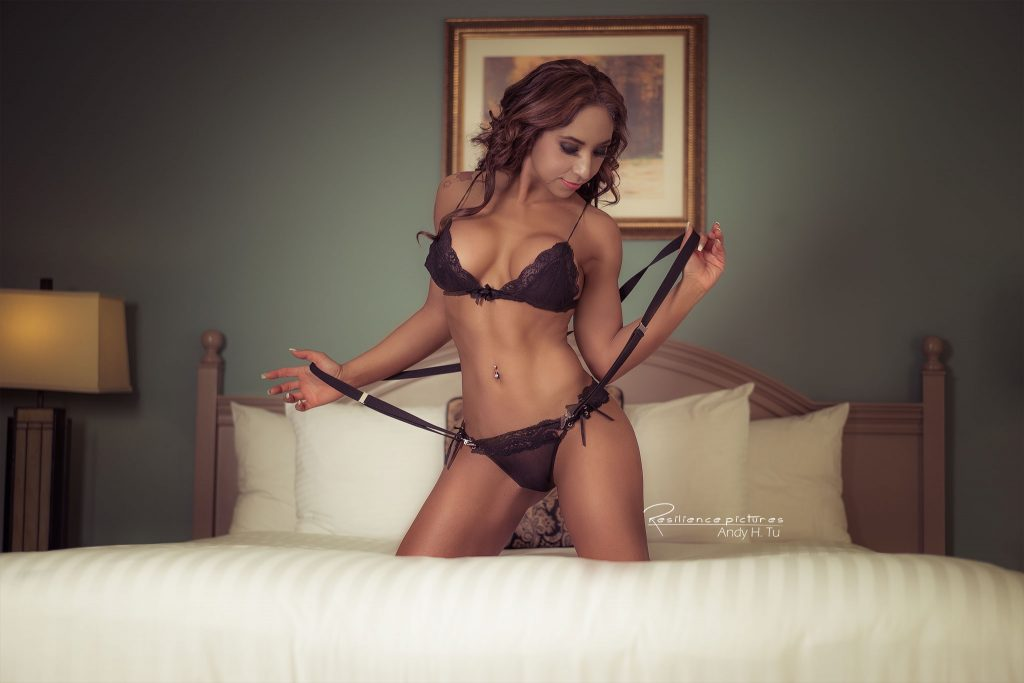 Model Black lingerie and suspenders on a bed, boudoir