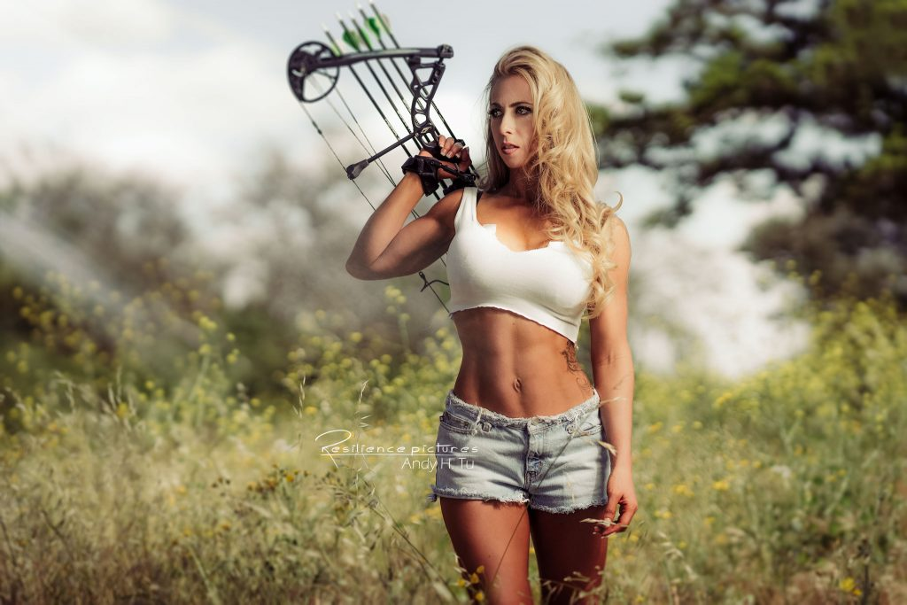 Blonde model with Hawk like eyes with a compound bow