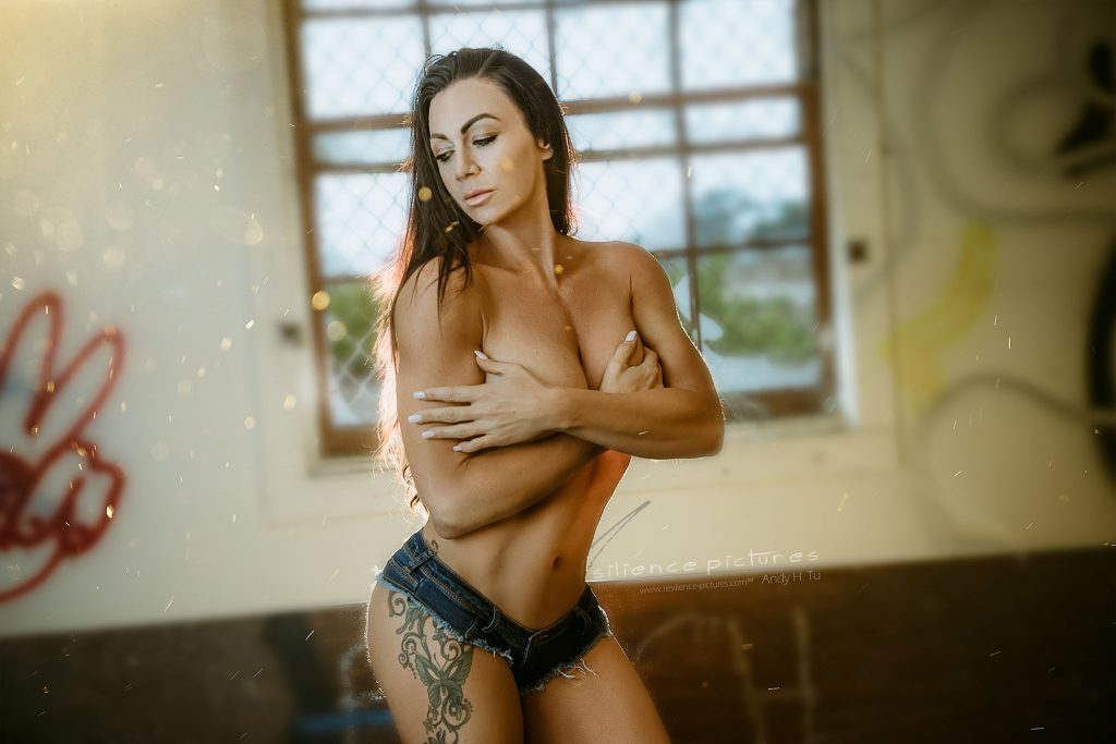 Brunette in Short shorts and topless posing in sunny abandoned building