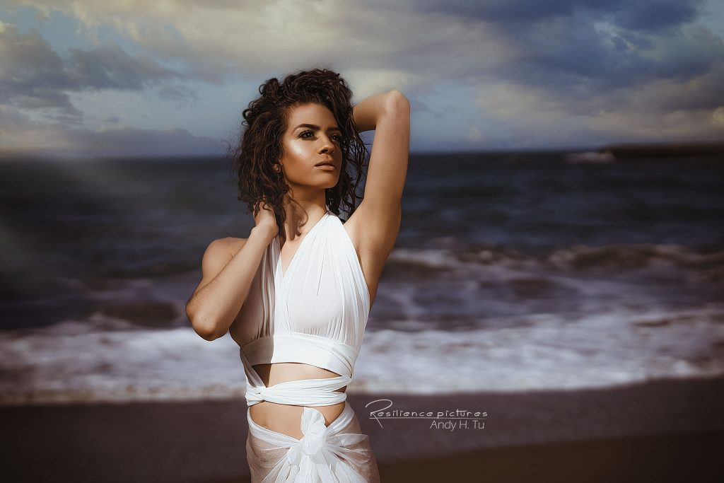 Portrait oft tan curly hair model in white draping dress at the beach
