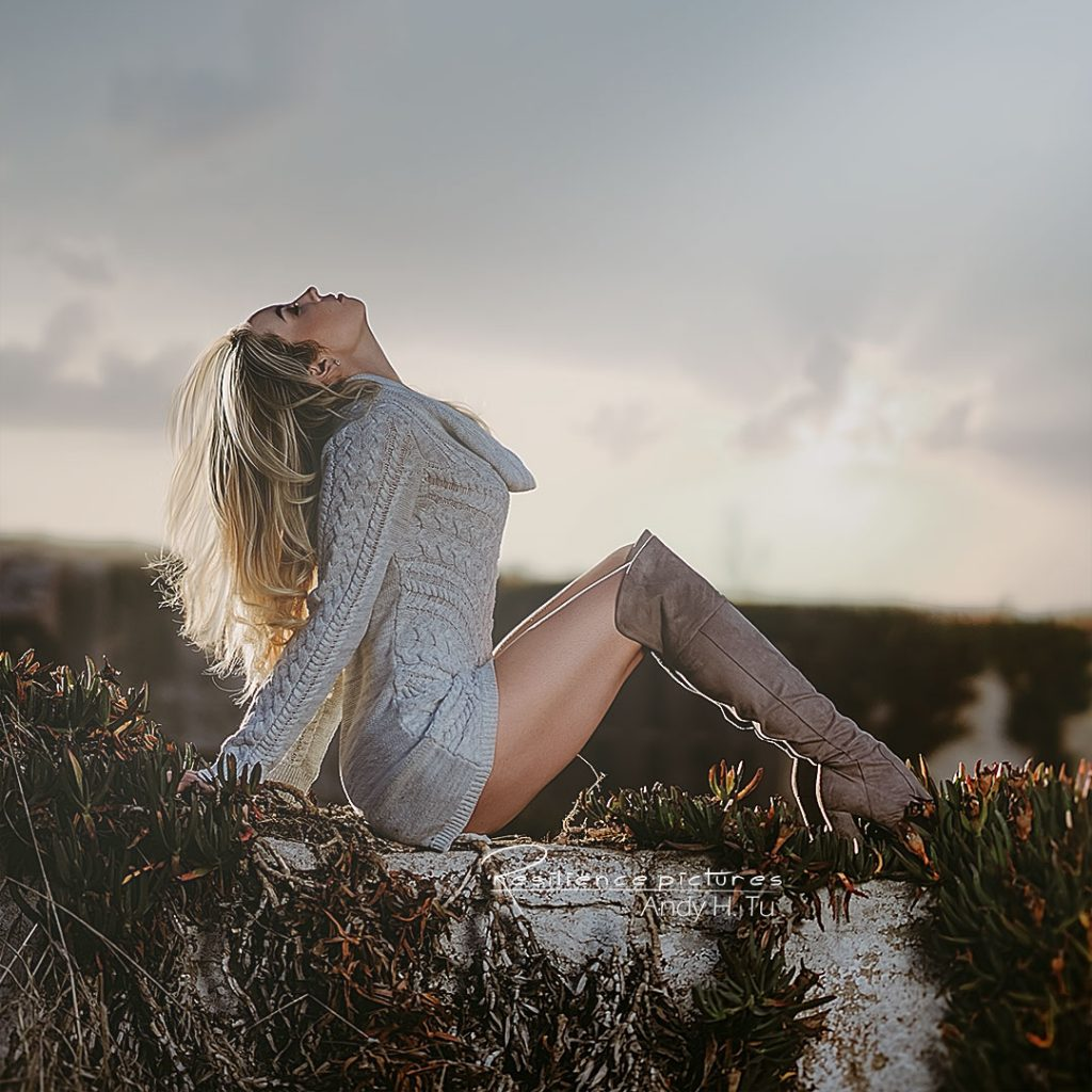 Girl with strong legs and long boots and white sweater, leaning back in the sunset.