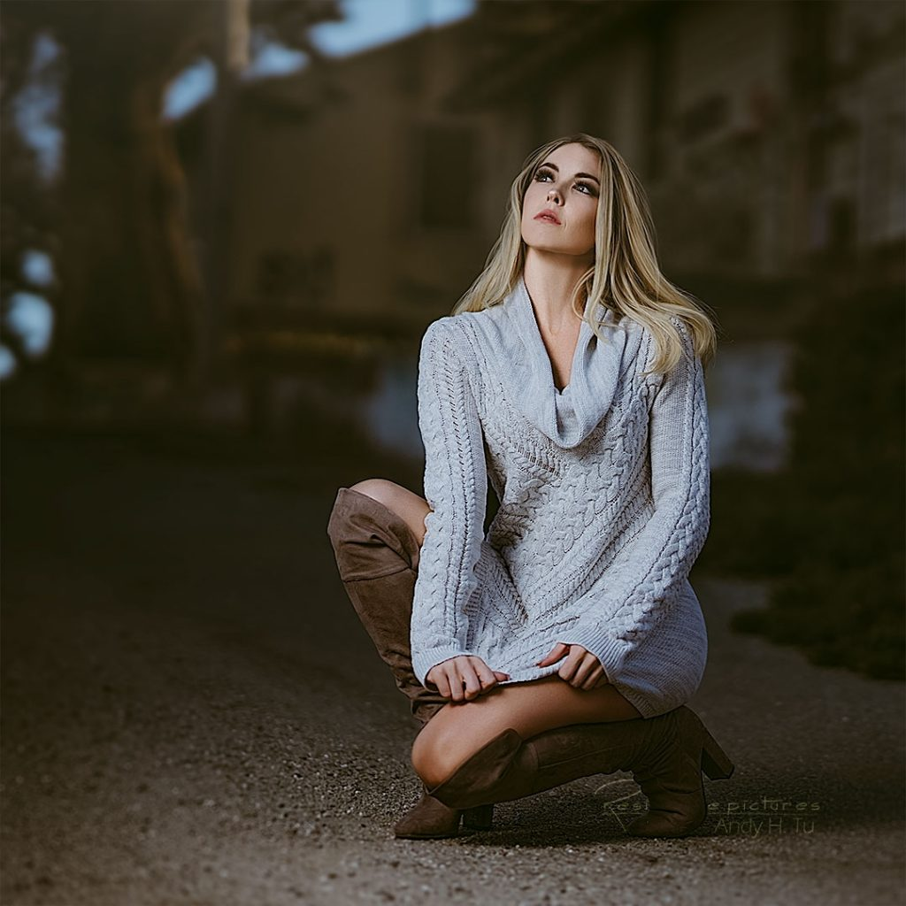 Long sweater girl in an abandoned place, kneeling down.