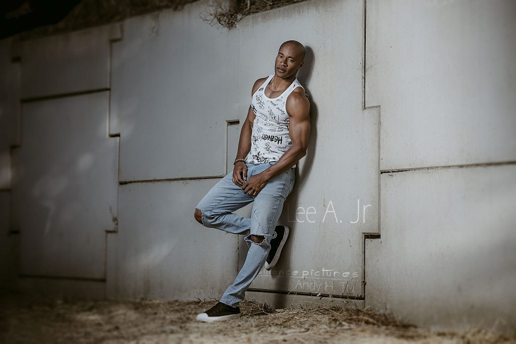 Muscular male model chilling against a wall