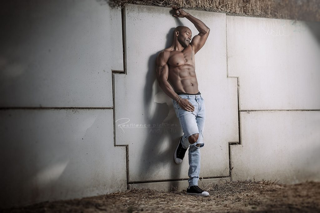 Shirtless male model relaxing against the wall in blue jeans