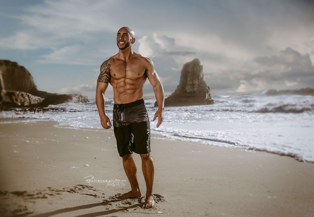 Bodybuilder smiling at the beach