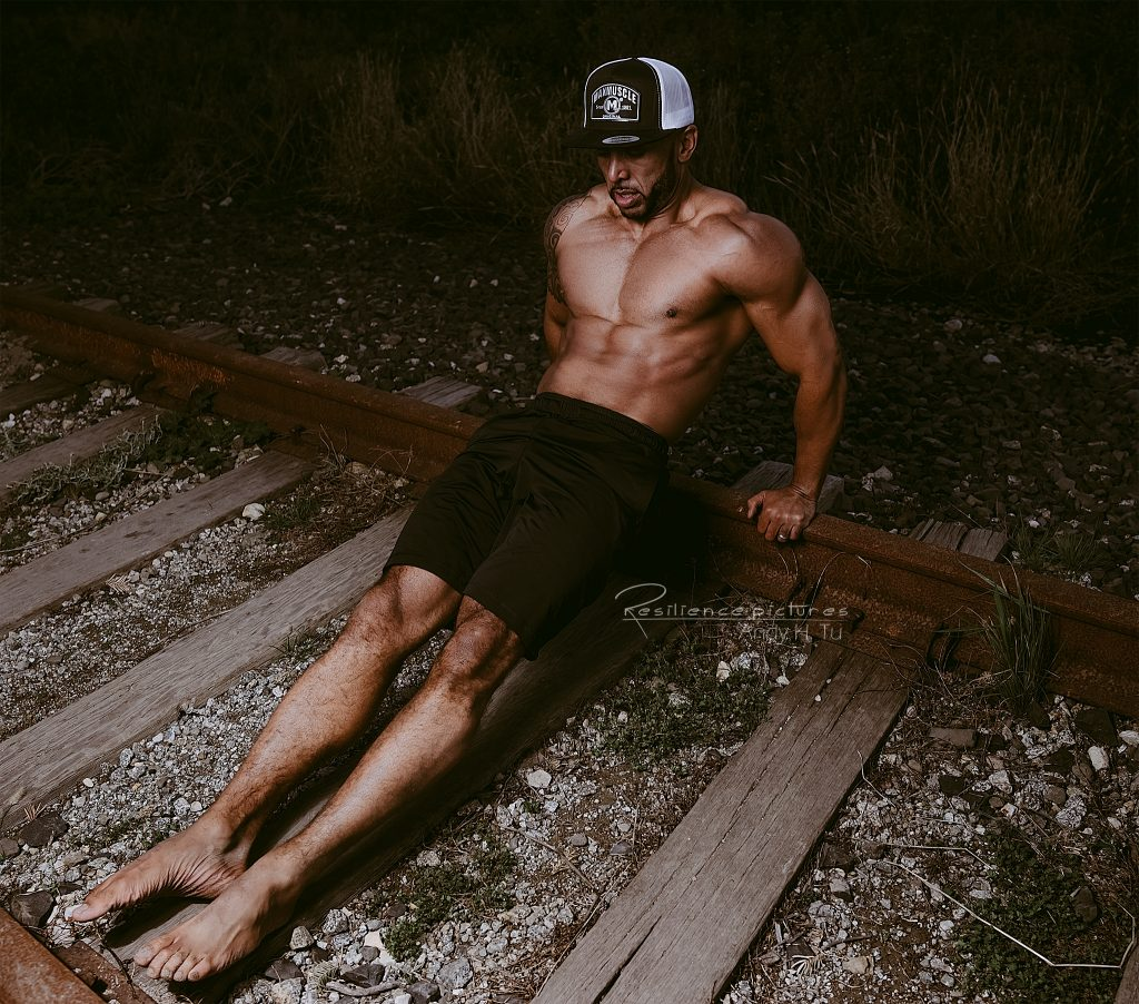 Max Muscle athlete doing dips on train track