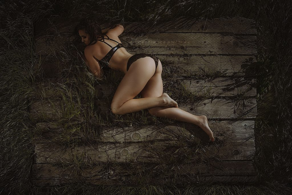 The Sleeping Beauty Boudoir model in black lingerie on a wood platform no where.