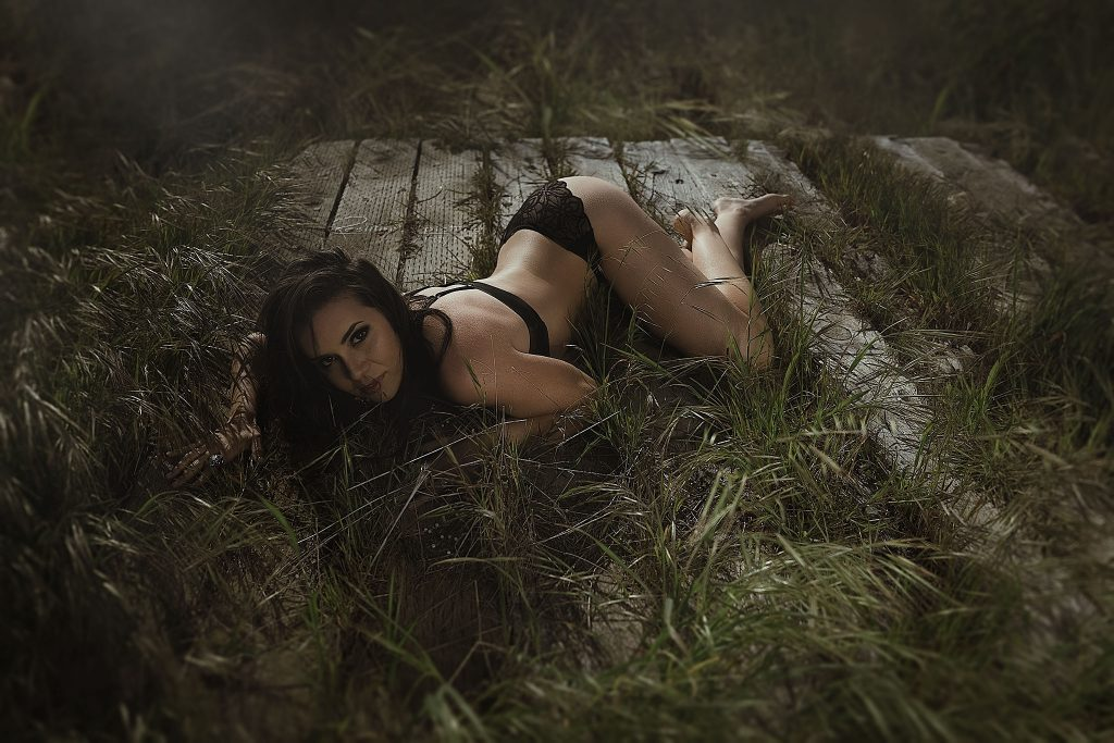 black lingerie brunette on wooden platform in grass