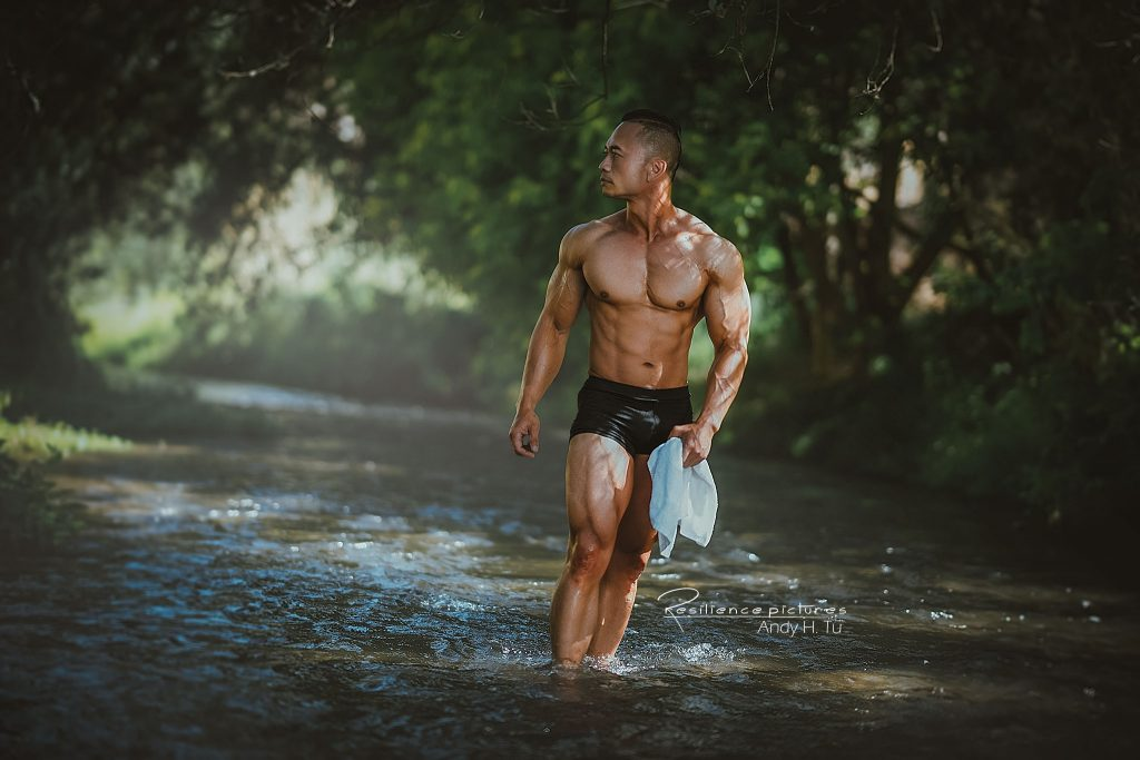 asian bodybuilder walking in the river