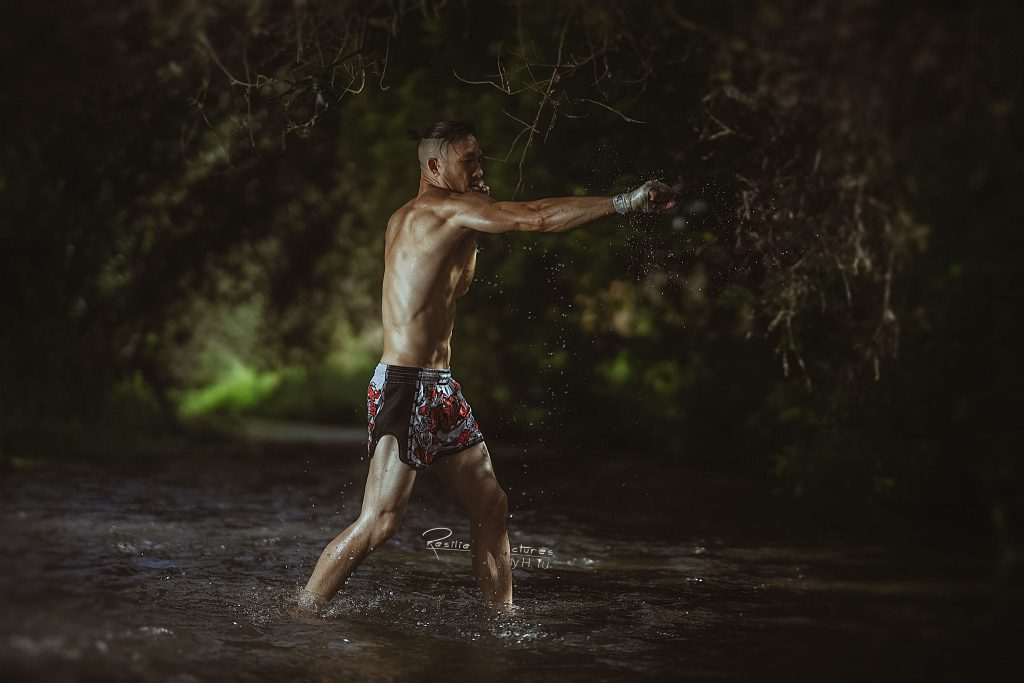 Muay thai fighter throwing a cross in the water