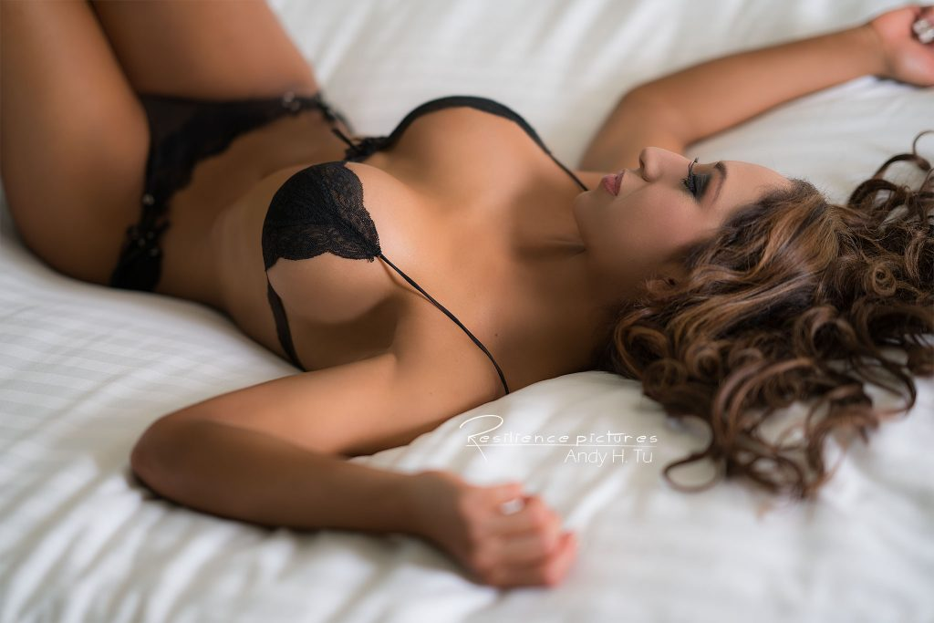 Black lingerie model on white sheets