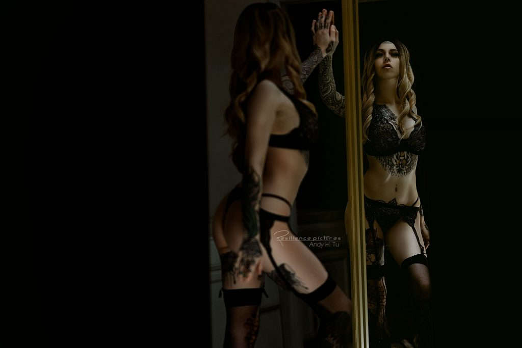 tattoo model touching a mirror in black lingerie