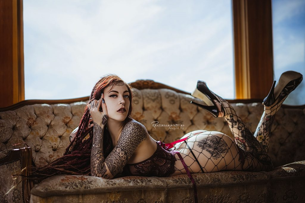 Cute Tattoo model with dreads lying on her chest in fishnet