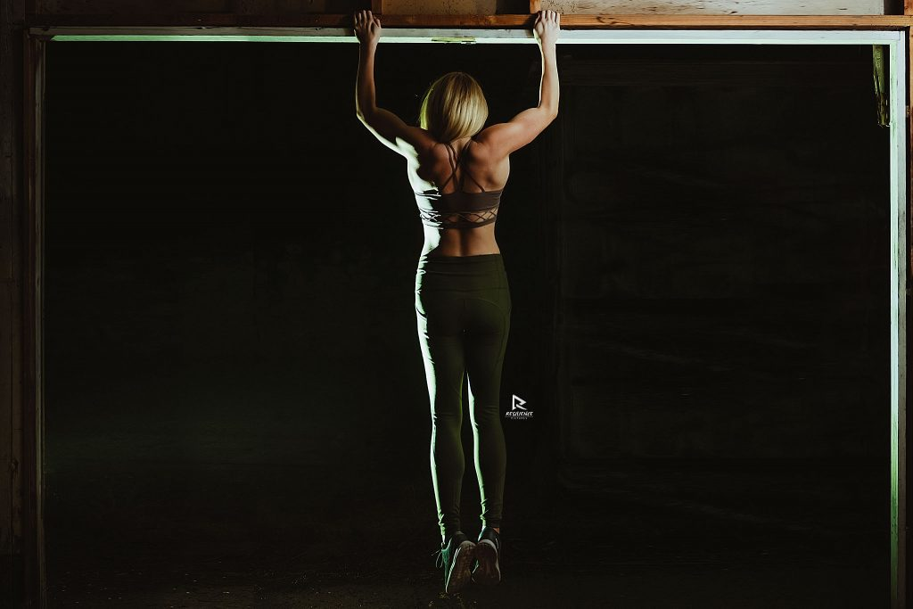 Fit blonde girl doing pull-ups in the dark