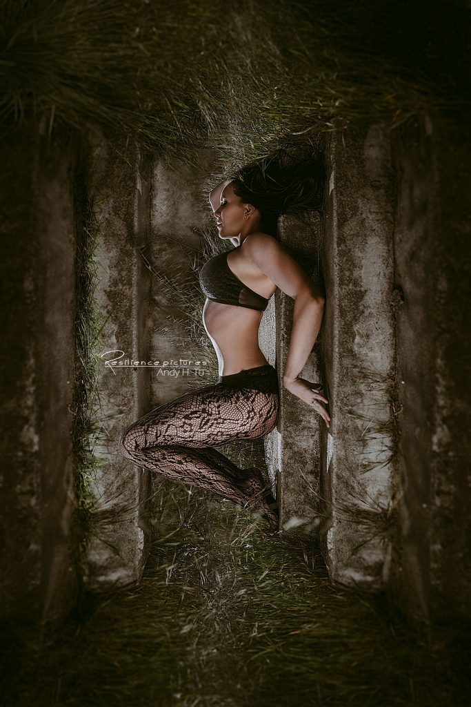 Sleeping Beauty in Black Laced Stockings and lingerie on stone steps.