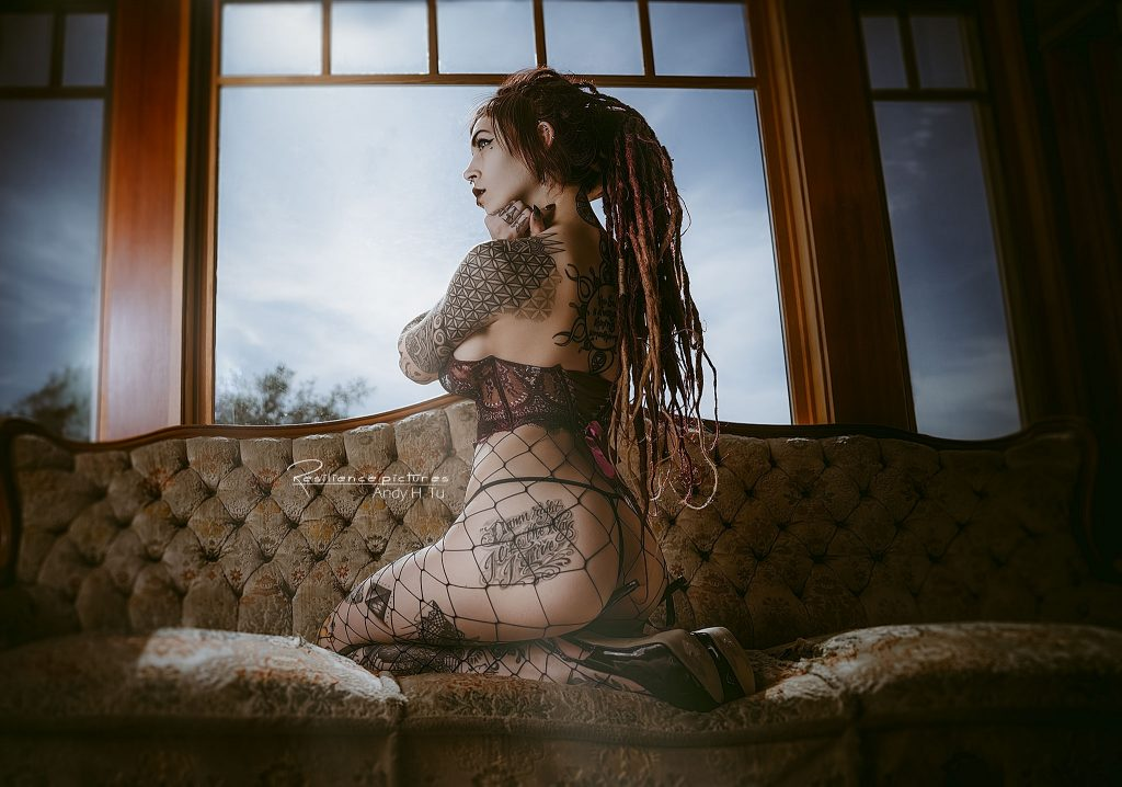 Tattoo model with dreads in fishnet lingerie