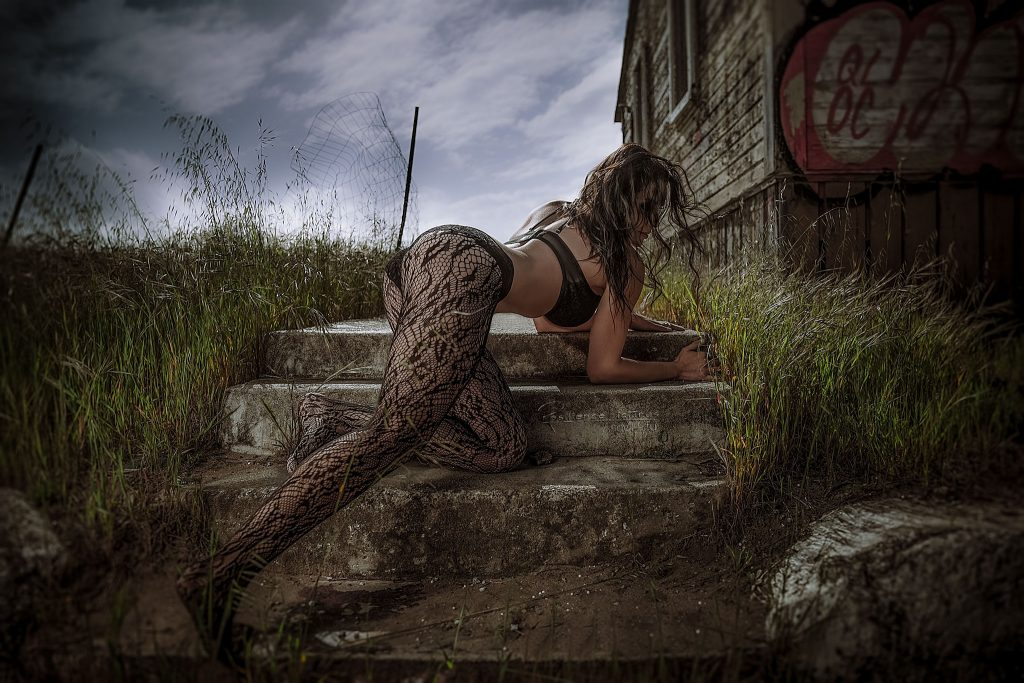 Fit Girl crawling up a stone path of open field