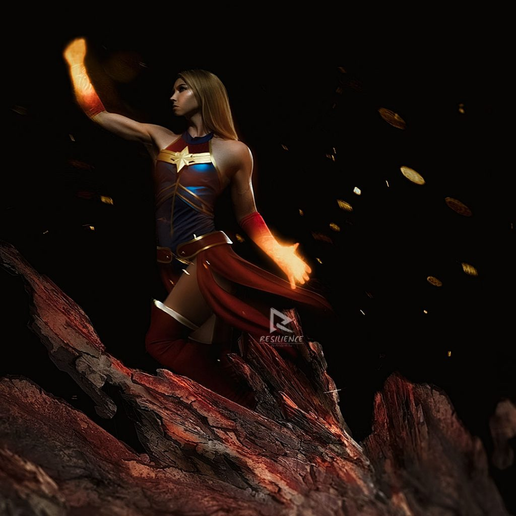 Ms Marvel flying off the g round with glowing fist. Cosplay Design by Sinde