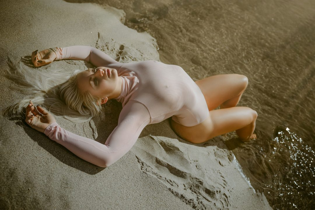 beautiful-blonde-model-catching-sun-rays-on-the-sand