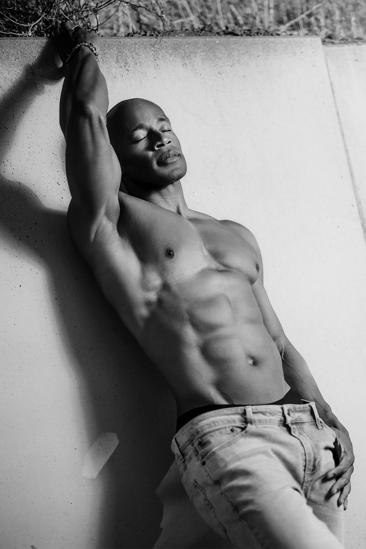 black-shirtless-male-calvin-klein-model-relaxing-on-the-wall-casting-shadows
