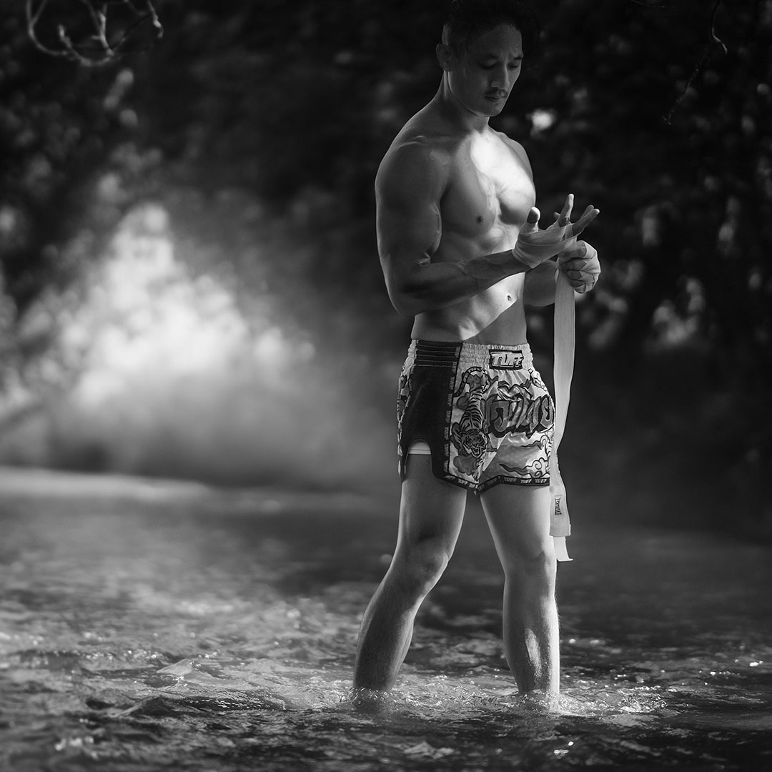 muay-thai-warrior-wrapping-his-fist-in-the-swamp